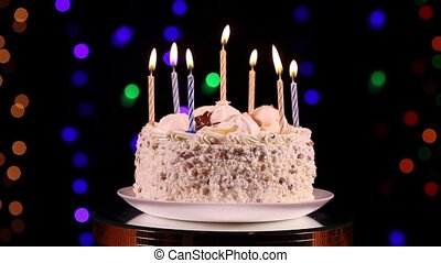 Happy Birthday cake with burning candles rotating in front...