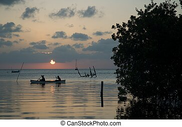 Belize canoe - A canoe glides past as the sun sets over Caye...