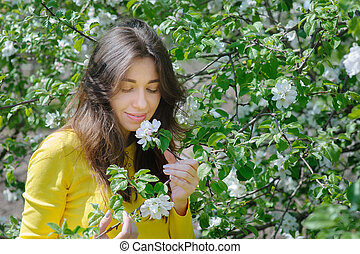 Beautiful woman smelling a flower in the spring garden