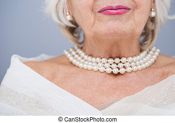 I love my jewellery - Senior woman with valuable pearl...