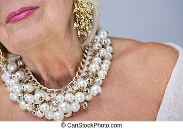 Rich and proud of it - Elderly woman with precious pearl...