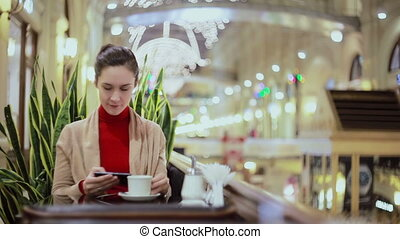 Woman using smartphone, drinking coffee in cafe.