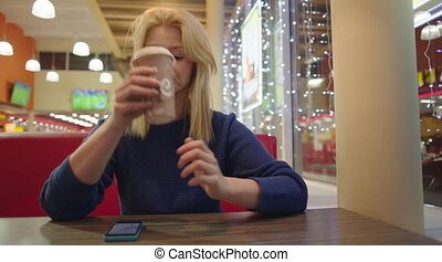Young Woman in Cafe Drinking Coffee from Paper Cup - Young...