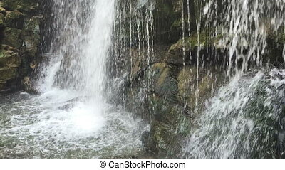 Cinemagraph - Big waterfall flows down the rocks mountains....