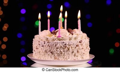 Happy Birthday cake with burning candles in front of black...