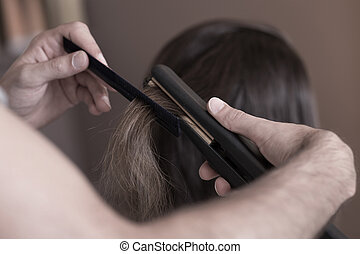 Hairdresser using a hair straightener - Close up of...