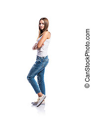 Standing teenage girl in jeans and white singlet, isolated -...