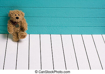 Teddy bear sitting on white wooden floor with blue-green...
