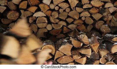 Man putting log on pile