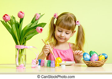 Child girl with brush coloring easter eggs