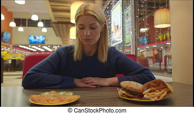 Young Woman Prefer Healthy Food - Young woman is sitting in...