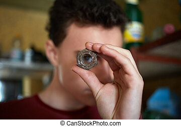 Teenager boy looking through a rusty screw nut - Teenage boy...