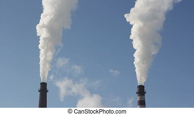 Cinemagraph - Factory chimney with smoke under blue sky -...
