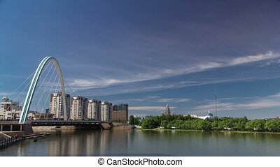 Bridge over Ishim with park timelapse with the transport and clouds on the background. Central Asia, Kazakhstan, Astana
