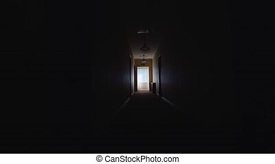 Silhouette of a man walking along a dark corridor