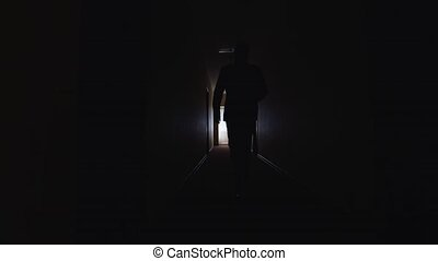 A man walks down the dark corridor