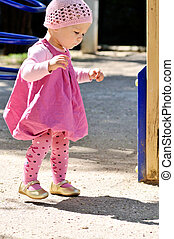 first steps of baby girl on the playground