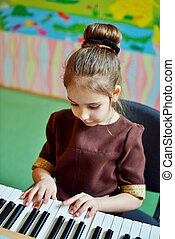 girl playing  piano - little girl is playing on the  piano