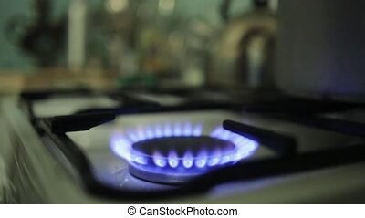 Putting huge aluminum saucepan on burning gas stove. Blue fire