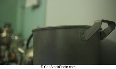 Putting huge old aluminum saucepan on burning gas stove. Blue fire