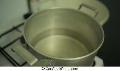 Man hand cover big saucepan with water on gas stove by old round drum plate.