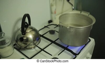 Man hand cover saucepan with water on gas stove by old round...