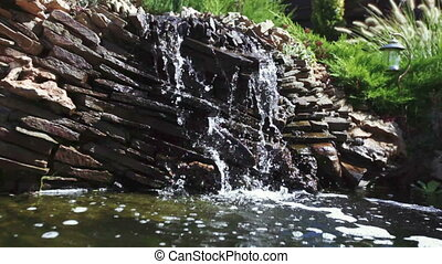 Artificial waterfall in park - Water flowing from under...