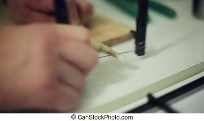 Man hands cut piece of drum stick by cheese cutter on wooden...
