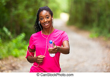 African american woman jogger holding a water bottle -...