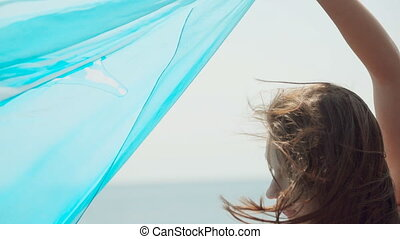 Slim woman dressed in an orange bikini standing at the beach with a light pareo in her hands in windy weather