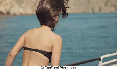 Cheerful girl with long black hair wearing a black bikini on...