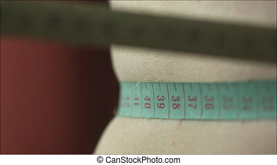 Drawing Tape Measure Tight over the Waistline - Closeup shot...