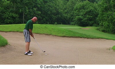 Golfer Uses Wedge In Bunker - Golfer uses sand wedge in...