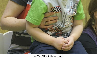 Little boy with mom sitting on the chair in kindergarten