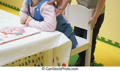 A little girl helps a little boy to sit on a chair in a...