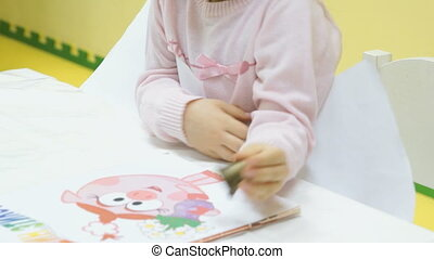 A little girl sitting on a chair in kindergarten HD