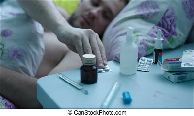 Sick Man in Bed Taking Pills - Young man is sick and lying...