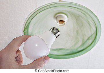 Close-up of energy-saving LED light bulb in human hand. -...