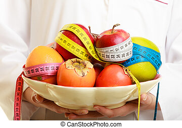 Woman holding fruits dietitian recommending healthy food. -...