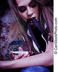 Portrait of woman addicted to syringe on brick wall...