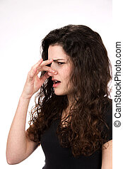 Woman Smells Something Stinky - Woman pinches her nose in...