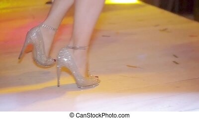 Dancing feet of go go dancer on high heels in nightclub. Red tippet. Slow motion