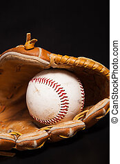Baseball and Glove - A baseball and glove on a black...