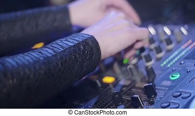 Hands of Dj girl mixing on stage of nightclub. Slow motion. Turntable