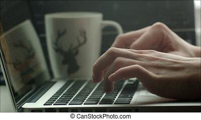 Man Typing in Laptop, Mug Standing Nearby