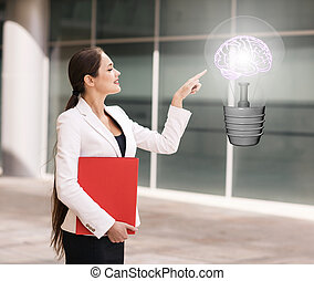 Business woman point on the big light bulb - Happy young...