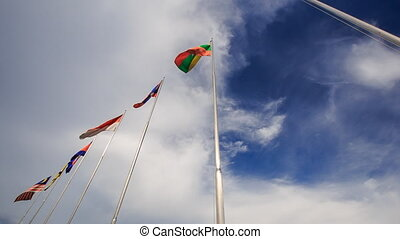 Many-colored Banners Flap on Flagstaffs Blue Sky -...