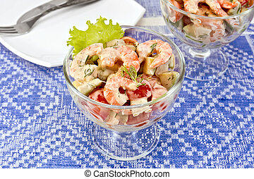 Salad with shrimp and tomatoes on blue tablecloth