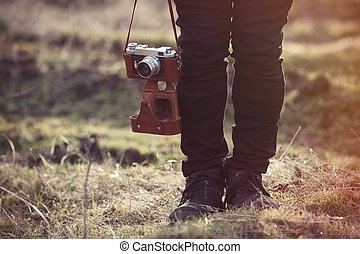 Foots and retro camera on strap near the ground