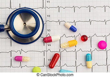 stethoscope and pills on an ekg - several tablets lie on an...
